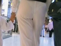 Hot mature babe in white pants in candid street video