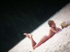 Hot body babe lying down on the beach surprised by a spy cam