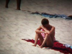 Nude sun tanning girls expose themselves to a beach spy cam