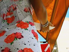 An inquiring camera looks under a white dress with rose print