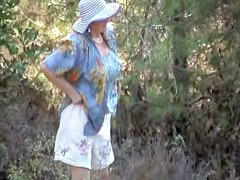 Smiling milf in big hat caught pissing outdoor