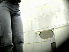 Blonde in glasses getting voyeured in the public toilet