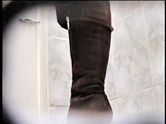 Amateur in high boots sits pissing in public toilet