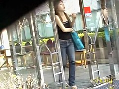 Slim Asian girl engaged into boob sharking on the street.
