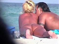 Hot beach handjob scene of tantalizing naked woman jerking husband.s penis