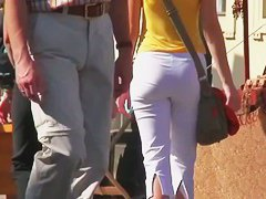 Sportive babe in white pants getting filmed while having a walk