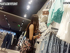 Beautiful young woman in mini-skirt caught in the clothes store