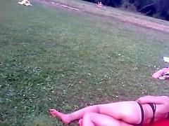 Girl in tiniest bikini getting sun tanned in the field PICT0011