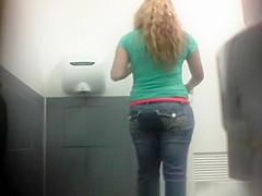 Blonde in jeans pants peeing in toilet