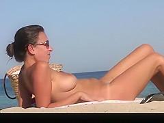 Long hair nudist woman dresses her bikini