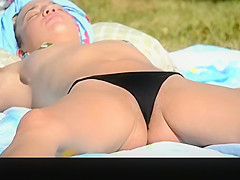 topless woman lying down in the grass sunbathing