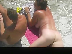 Nudist woman and man in rocky beach