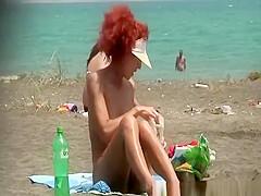 Redhead woman undresses bikini at beach