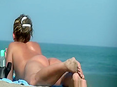 Nudist woman puts cream on her butt