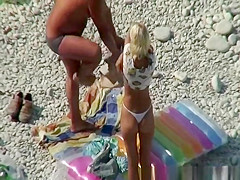 couple undressing in beach