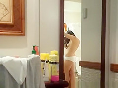 Girlfriend drying her hair in bathroom