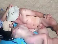 Nude woman strokes her man's penis at beach
