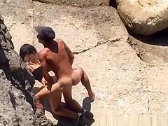 Couple spied in rocky beach having sex
