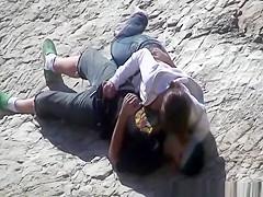 Girl masturbates her guy in the rocks