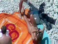 Group of nudists sunbathing in the beach