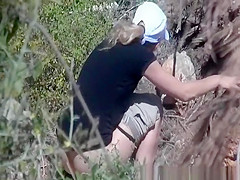 Blonde woman in shorts caught peeing in the nature