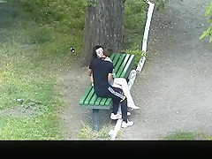 Teen couple making out in public park bench