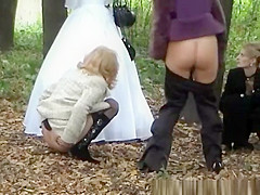 Three ladies help bride pee outdoors