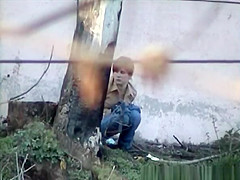 Girl pees next to big wall