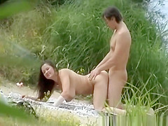 naturist couple spied in the nature by the river shore