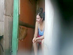 girl caught peeing in an old wood toilet