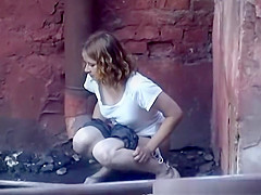 girl pees in public next to old buildind