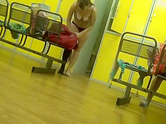 Pregnant woman undressing in locker room