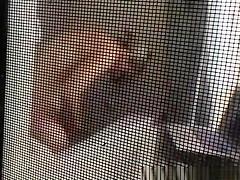 Voyeur secretly films his milf neighbor through window