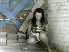 Cute girl pissing on a street corner