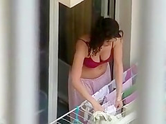 Lovely neighbor girl is hanging clothes