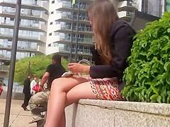 Leggy girl sitting on a wall