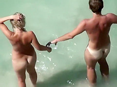 naked couple stepping in the water