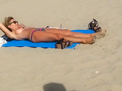 Adorable topless girl with big boobs enjoys the sun