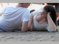 Sensual brunette looker with big tits talks with her friend on the beach