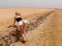 Naughty blonde uses the wind to expose her butt