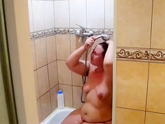 My plump wife washes herself in the shower
