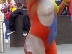 Nudist woman applies paint all over some men