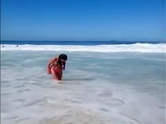 Large-assed harlot wears a flimsy bikini to the beach