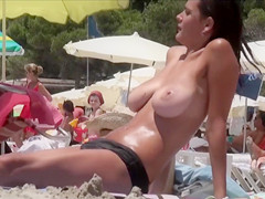 Busty babes are not wearing their bikini tops at the beach