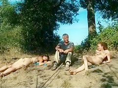 Old daddy sits with young hotties on the beach