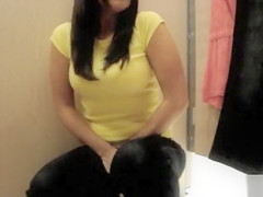 Desperate girl peeing into her shoe in a dressing room