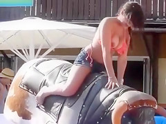 Bikini girl rides mechanical bull outdoors