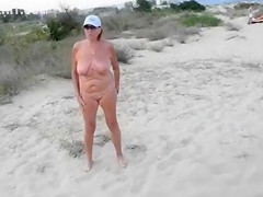 Exhibitionist wife is naked on the sandy beach