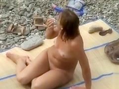 Nudist family alone on the beach relaxes all day