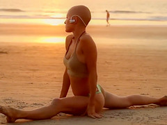 Bald beauty doing yoga by the sea